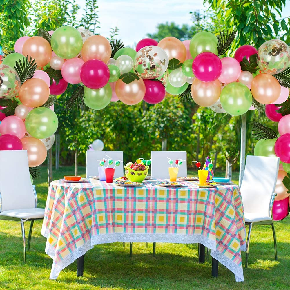tropical balloon garland set up over a party table