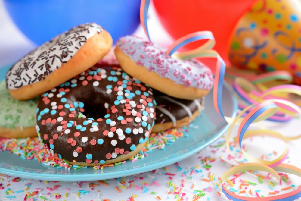 donuts covered in sprinkles on a plate with streamers and confetti