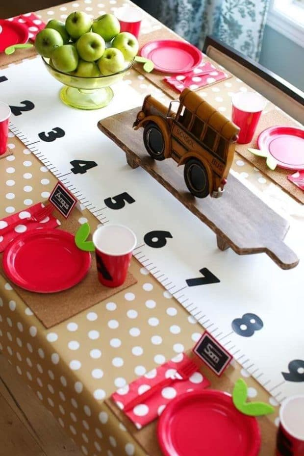 back to school party with apple plates and a ruler table runner