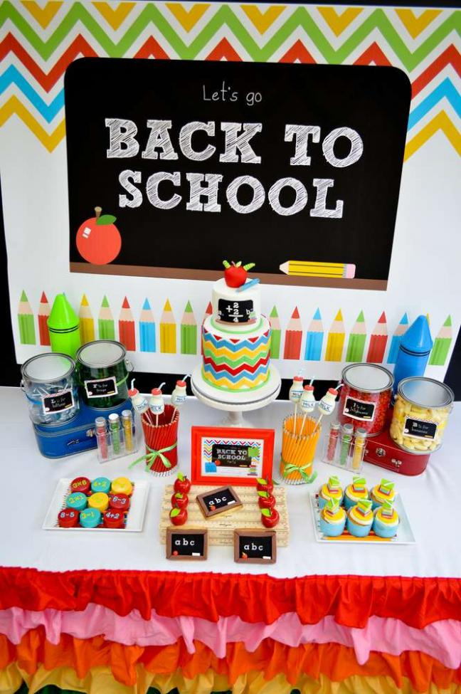 back to school party dessert table with cake and cupcakes