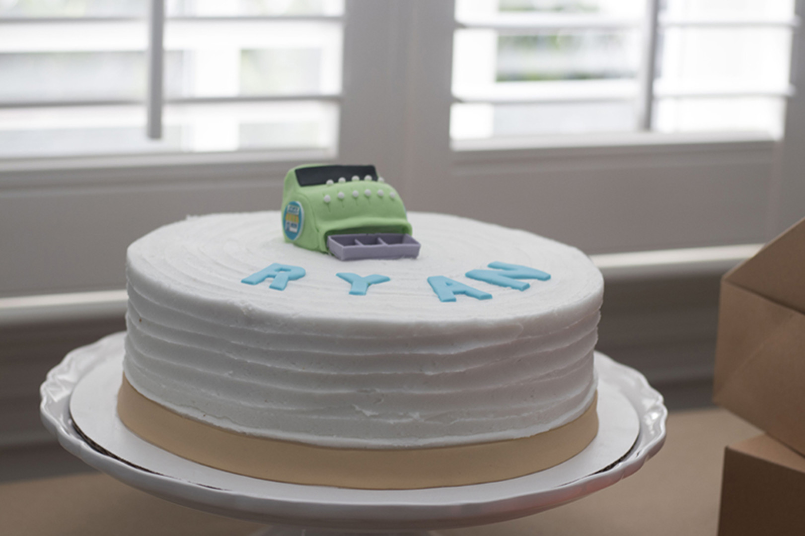 first birthday cake with green cash register on top