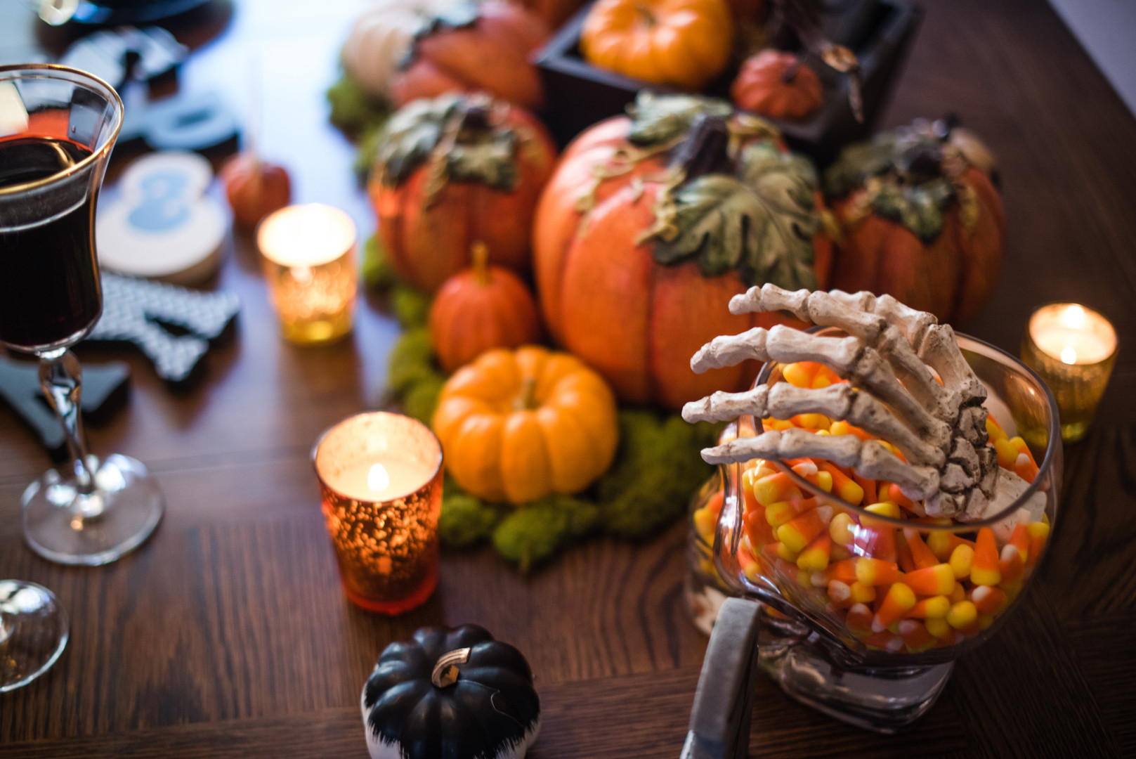 candy corn in a skeleton jar with pumpkins on a table