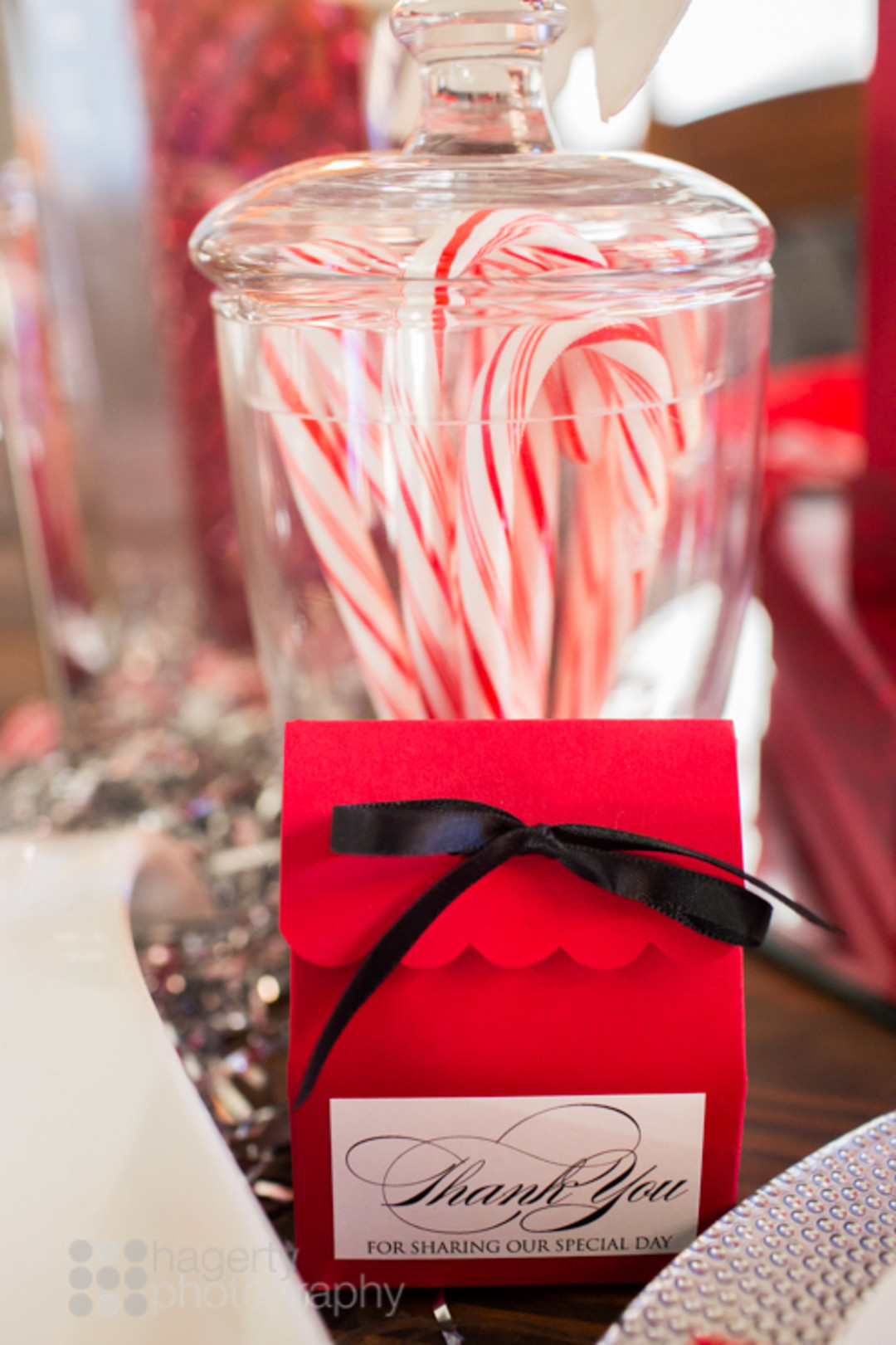 candy canes in glass jar and red favor box tied with black satin bow