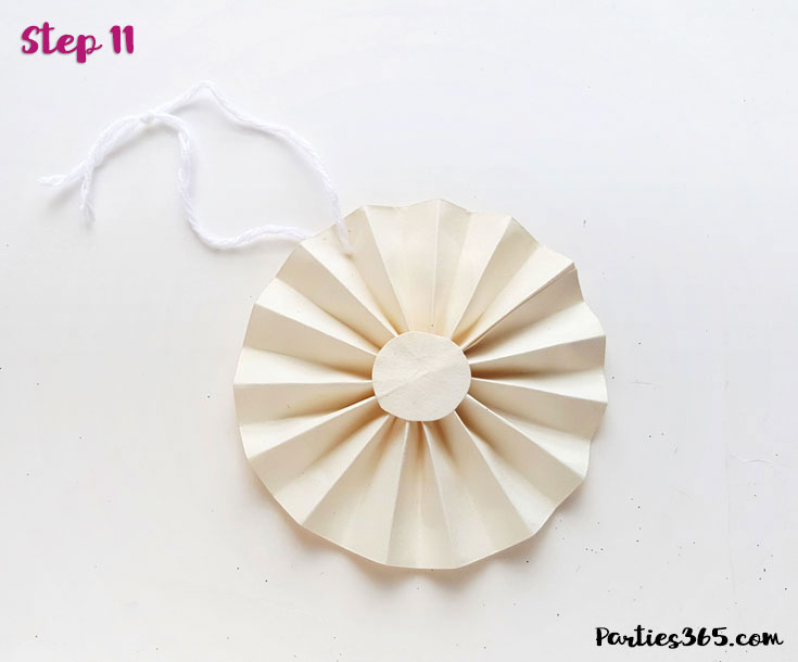 white paper fan ornament with string