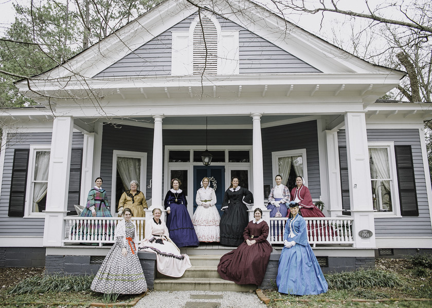 ladies in vintage dresses on front porch of historic home