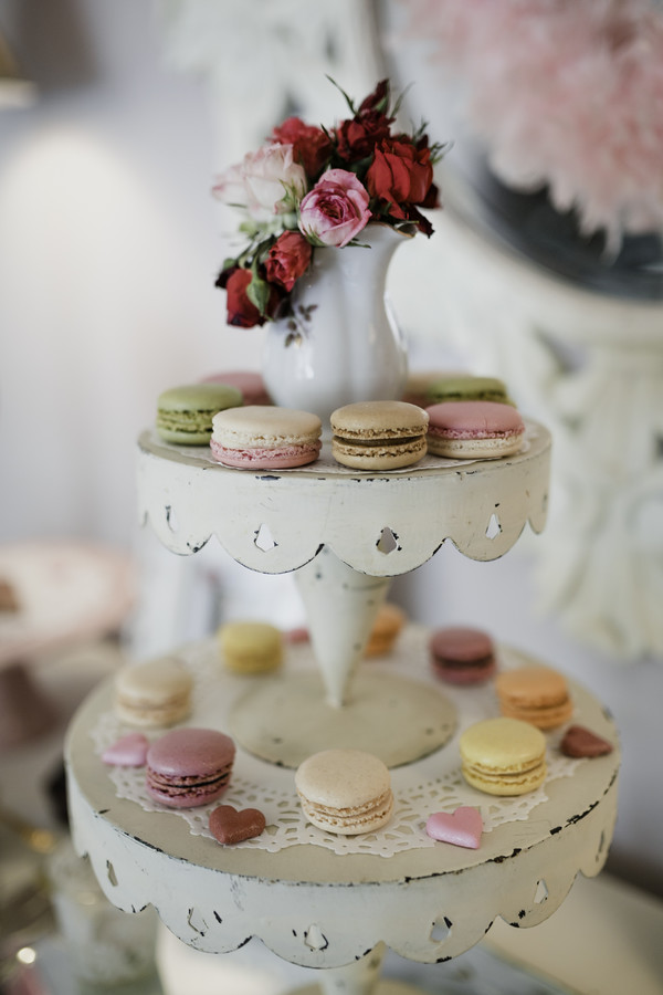 macarons on white tiered tray with pink flowers for galentine's day tea party