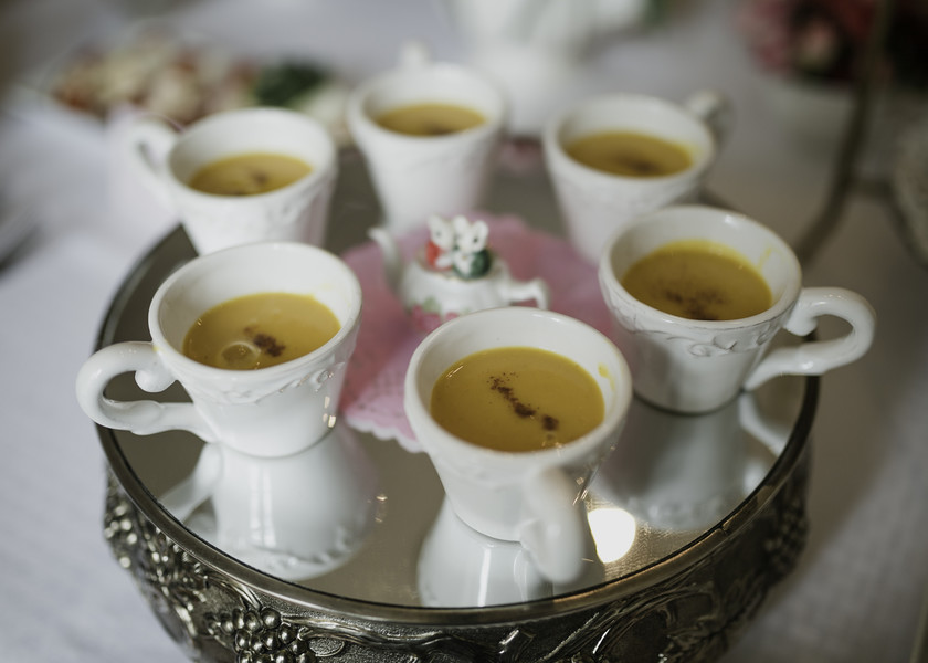soup served in tea cups at tea party on silver tray