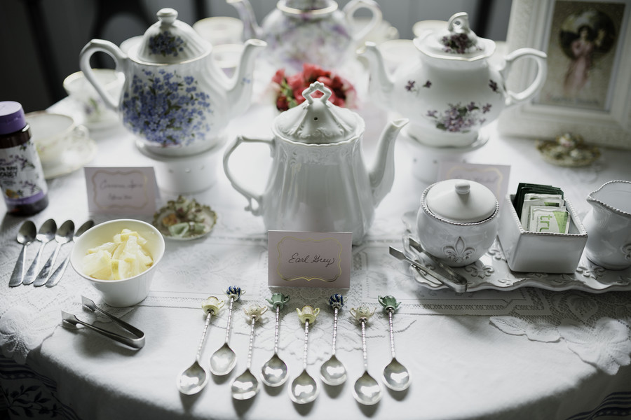 vintage tea pot and tea cups with spoons on a white lace tablecloth