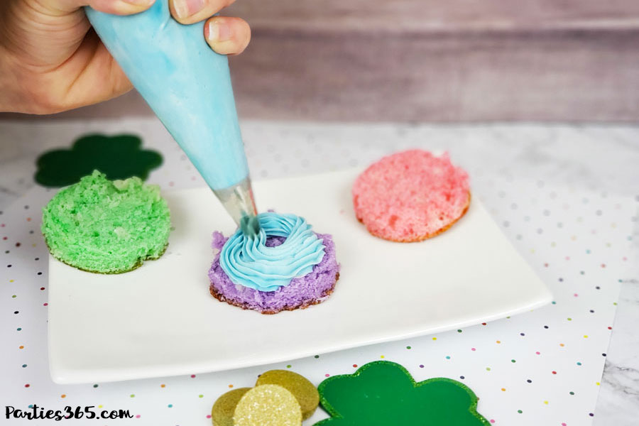 Learn how to make a cute rainbow mini cake for St. Patrick's Day or a unicorn birthday party! This DIY mini cakes tutorial, with frosting and recipe ideas, is sure to wow your guests! #rainbowcake #stpatricksday #unicorn #birthday