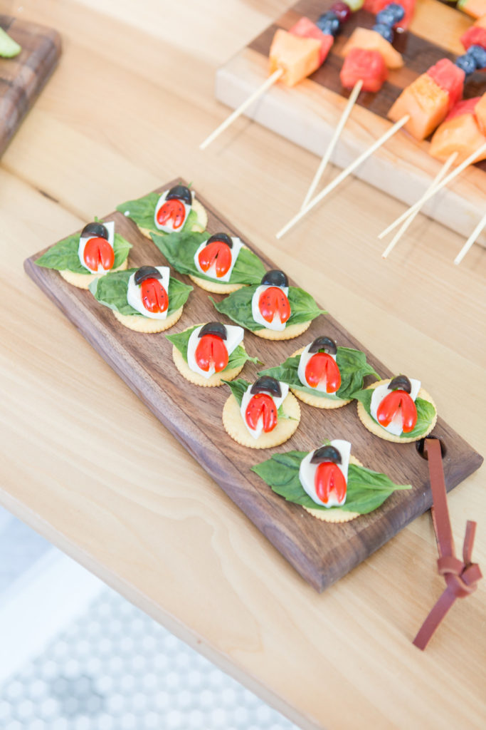 ladybug caprese salad on wooden tray at birthday party