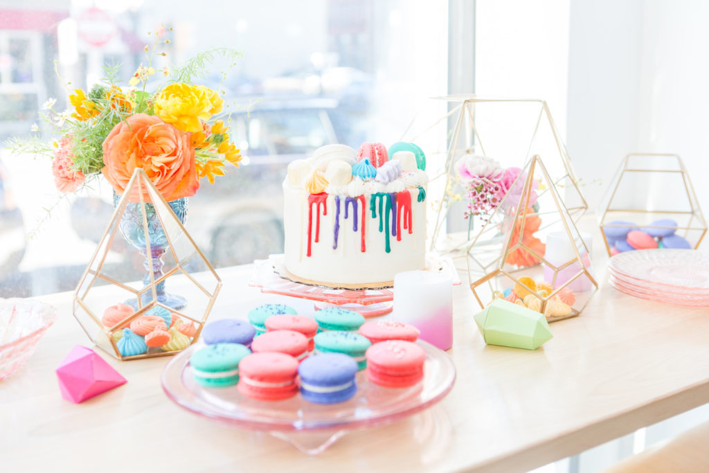 colorful spring dessert table at birthday party with cake and macarons