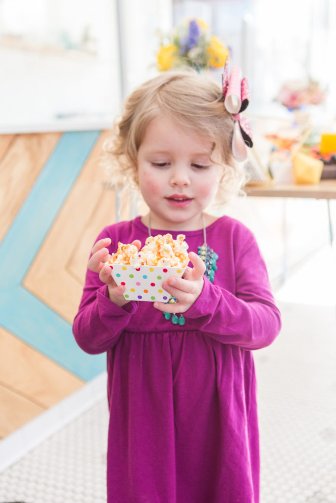 little girl with caramel popcorn at birthday party