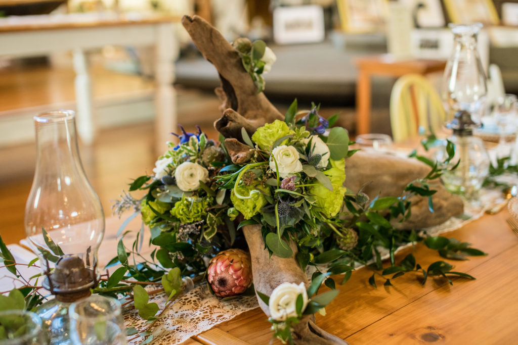 driftwood centerpiece with florals on wooden table
