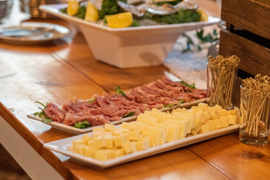 meat and cheese platter on wooden table at dinner party