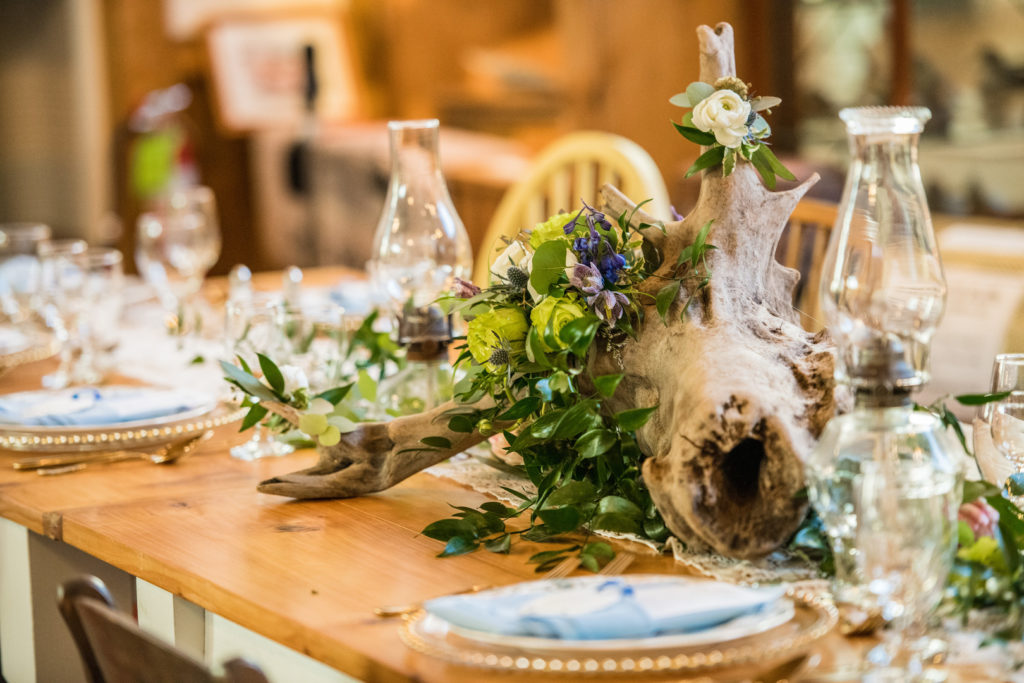 drift wood centerpiece with florals on table