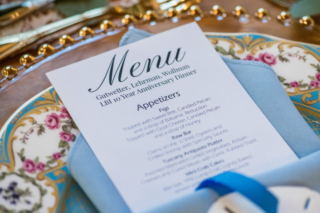 custom dinner party menu tucked inside blue linen napkin
