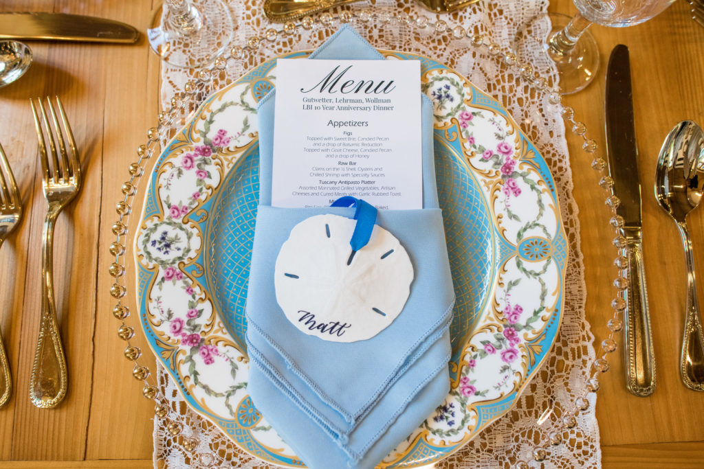 sand dollar place card on blue linen napkin