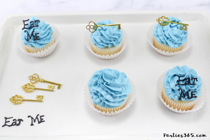 """These simple DIY cupcake toppers are perfect for your Alice in Wonderland theme party! The gold key and """"Eat Me"""" decorations are easy ideas to make your party food whimsical and fun for all ages! #AliceinWonderland #cupcakes #TeaPartyIdeas"""