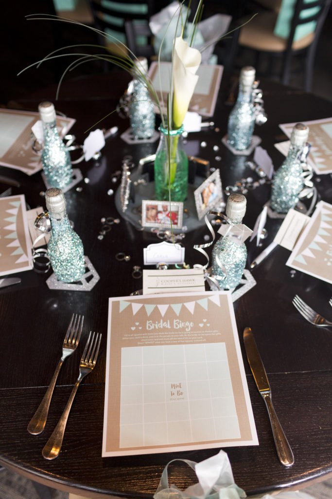 calla lily centerpiece at bridal shower with glitter champagne bottle favors