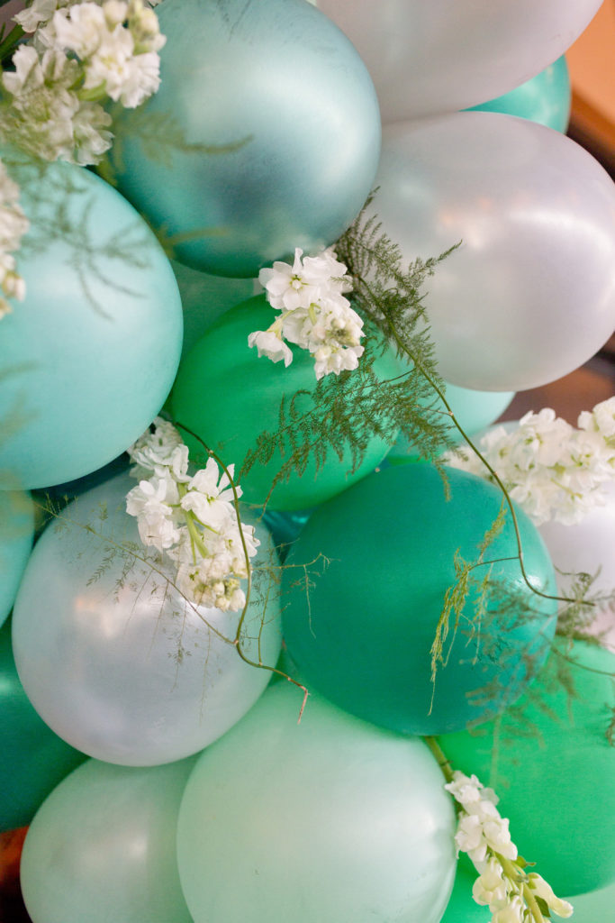 balloon arch in shades of green and silver with white flowers at bridal shower
