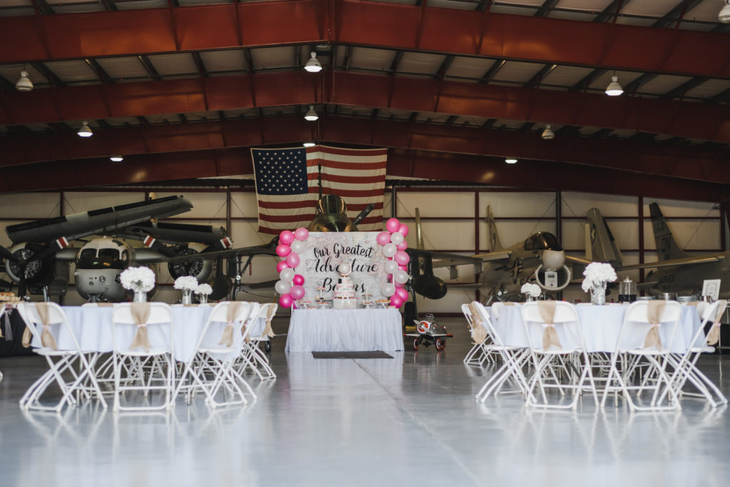 travel themed baby shower setup in airplane hanger