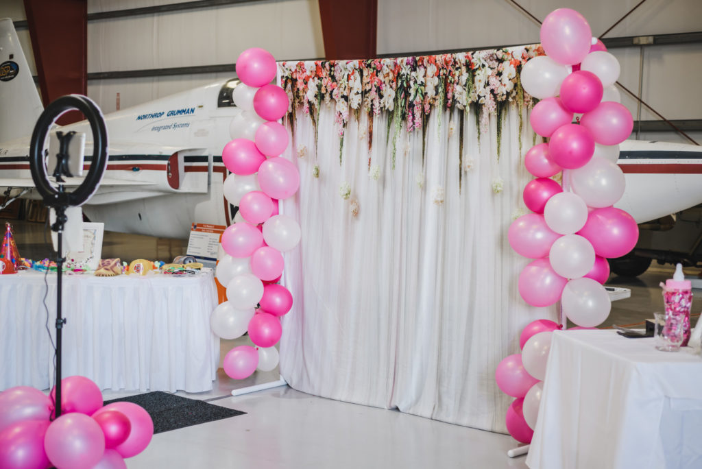 photo backdrop with pink balloons at baby shower