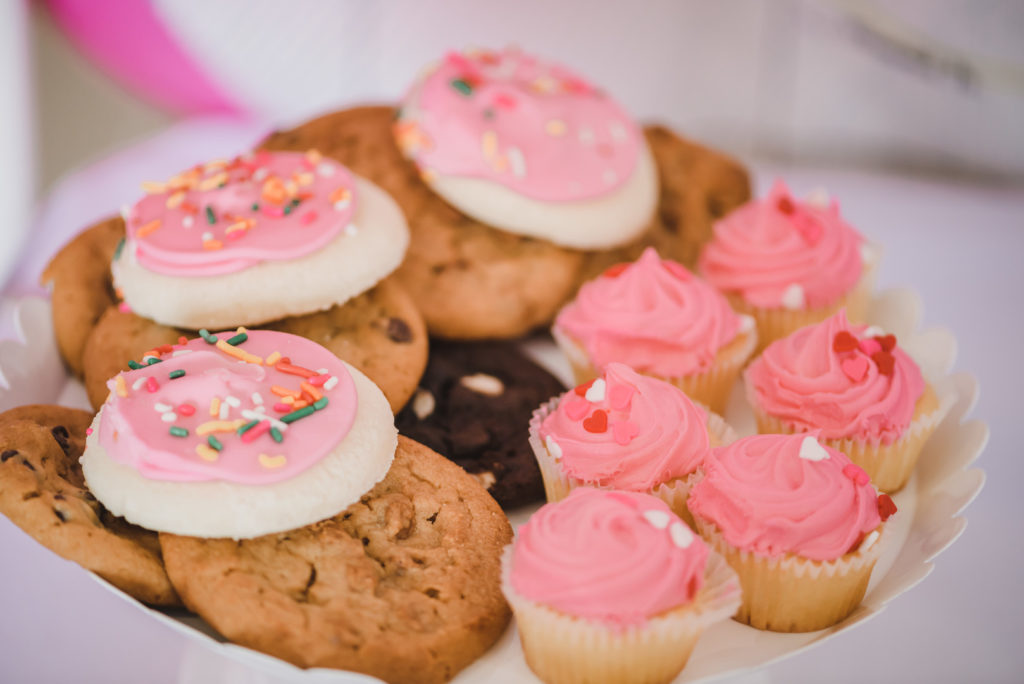 pink cookies and cupcakes for baby shower