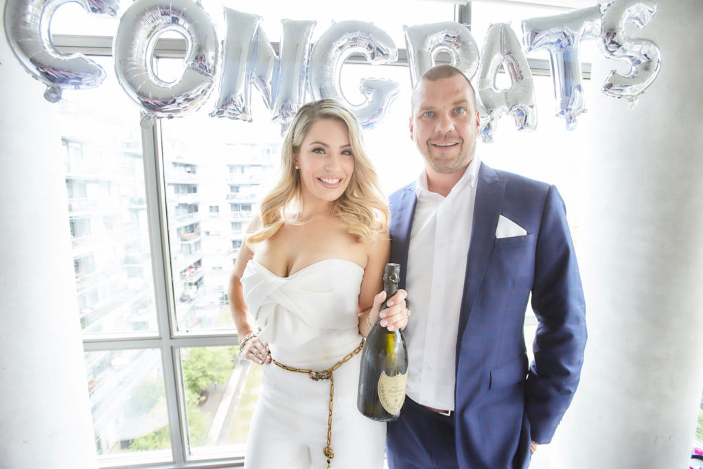 engaged couple with bottle of champagne under silver congrats balloon banner