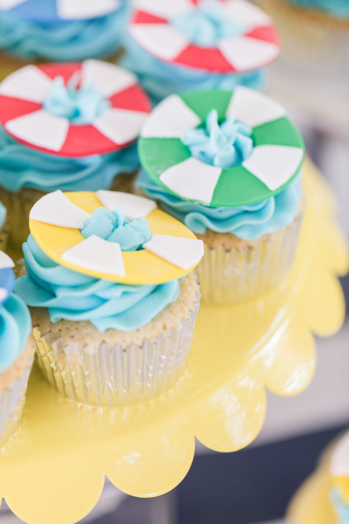 cupcakes with blue icing topped with lifesaver cupcake toppers
