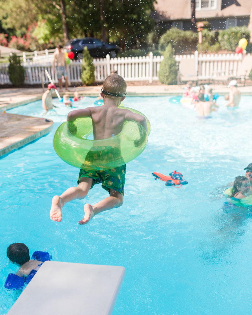 child jumping off diving board into pool with green inflatable float