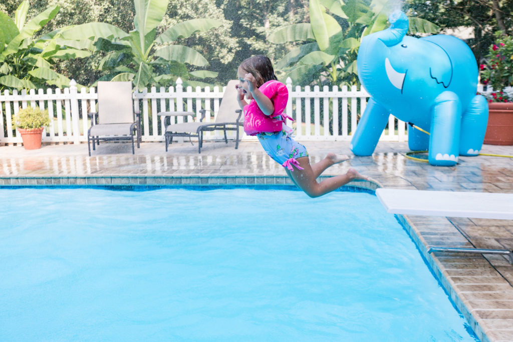little girl jumping into pool off diving board next to giant elephant sprinkler