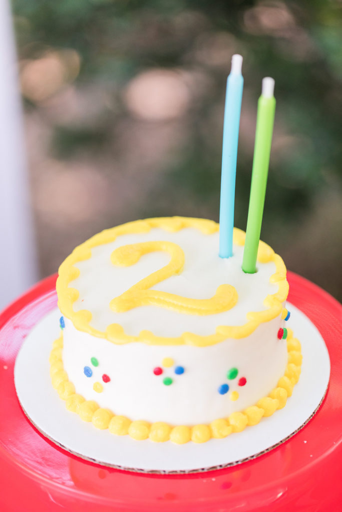 2nd birthday party cake with yellow icing and candles