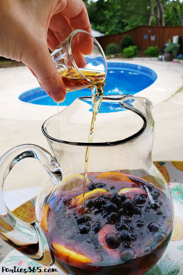 pouring bourbon into red wine sangria