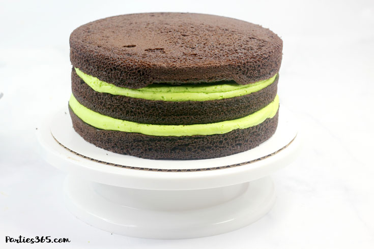 three chocolate cake layers with green icing