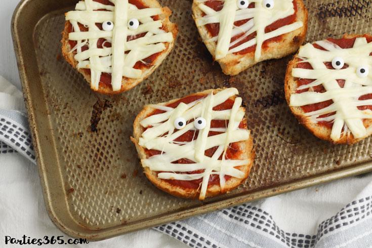 Halloween Mummy Pizzas on a baking sheet