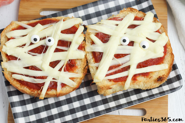 This super fun and easy Halloween Mummy Pizza recipe will be spooktacular for the kids! Whether you want to make a festive dinner for your family or something special for a Halloween party, these Mummy Pizzas are easy, quick and delicious! #Halloween #Halloweenrecipes #mummy #mummypizza #halloweenparty