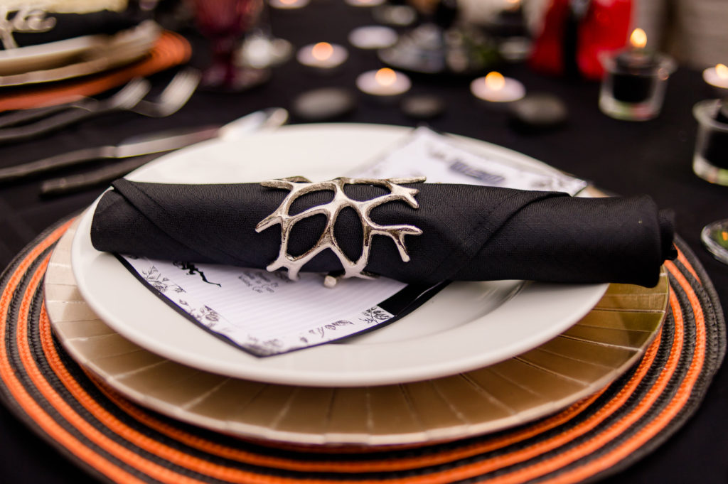 halloween black napkin with silver napkin ring on top of plates