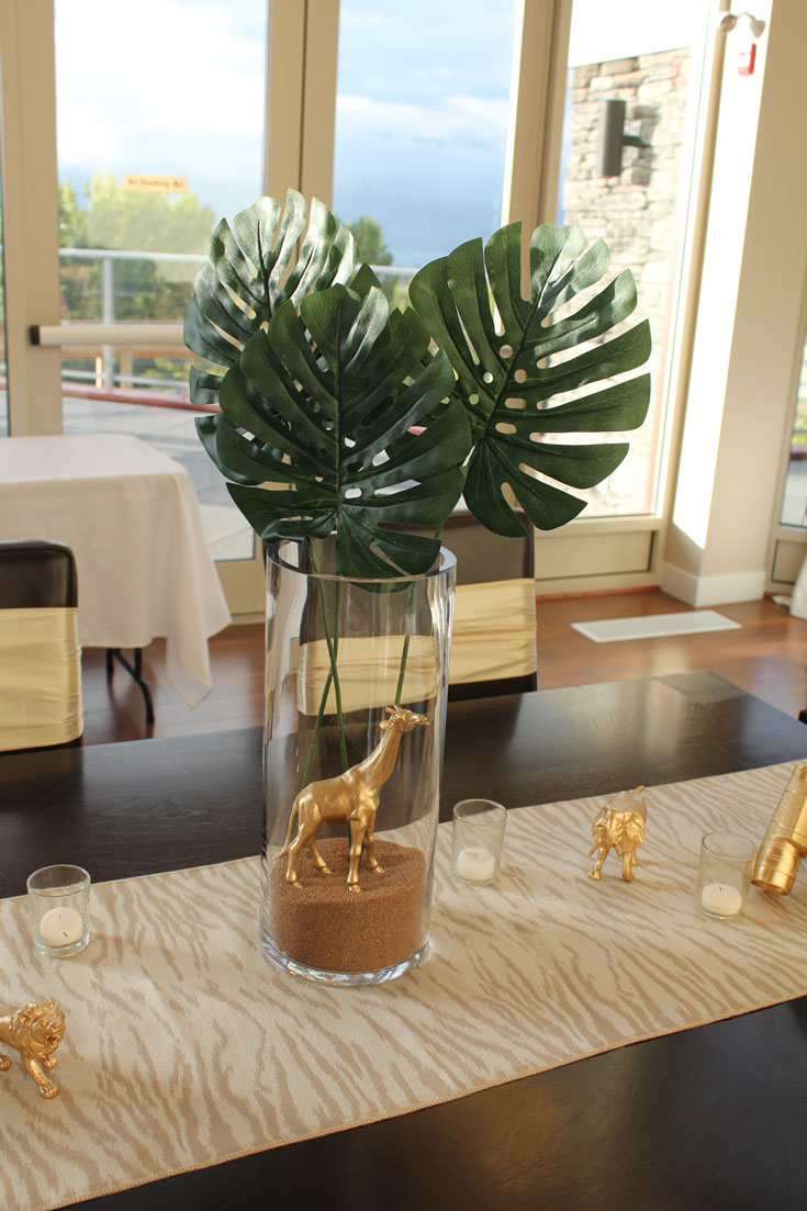 glass vase with palm leaves and gold giraffe at baby shower