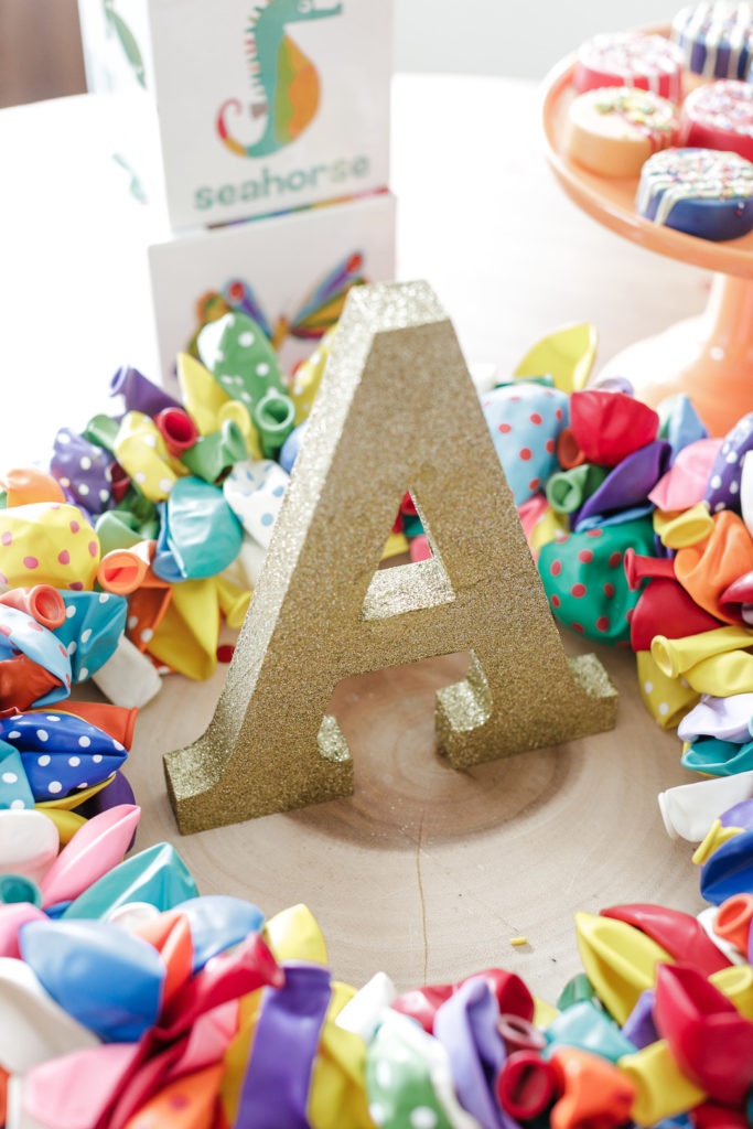 gold glitter letter A with balloon wreath for birthday party