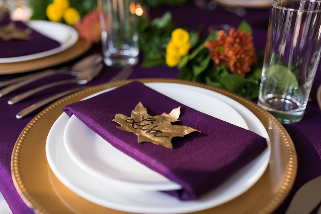 gold leaf place card on purple napkin