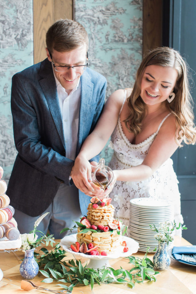 couple cutting belgian waffle cake at engagement brunch party