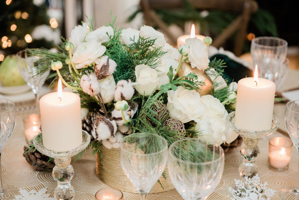 Christmas centerpiece with evergreen branches, pinecones and white roses