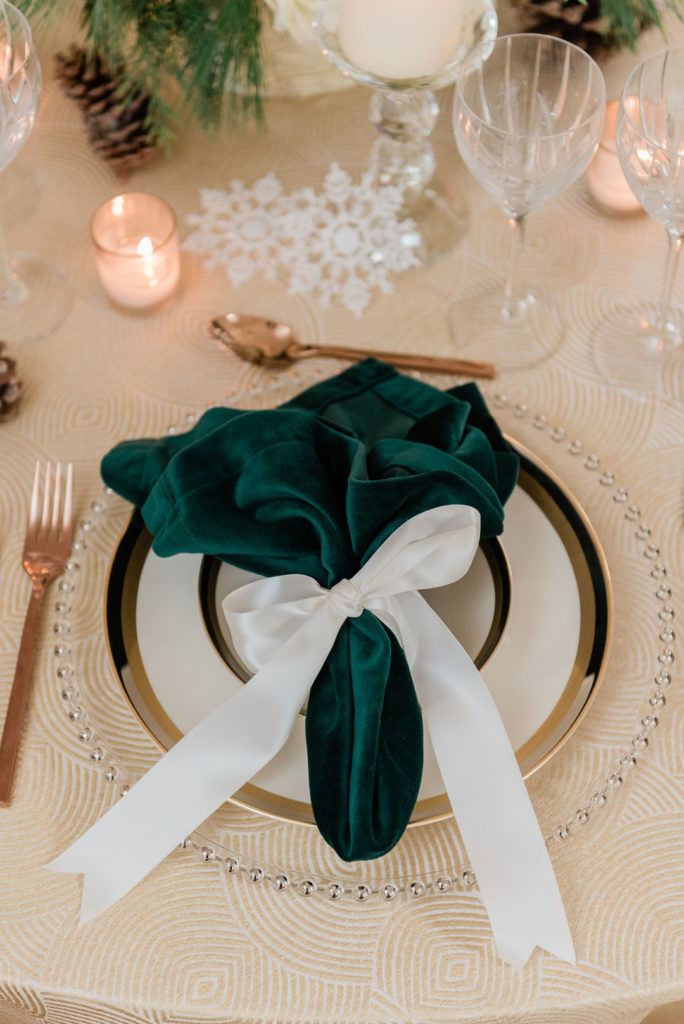 Christmas place setting with green velvet napkin tied with a white satin bow