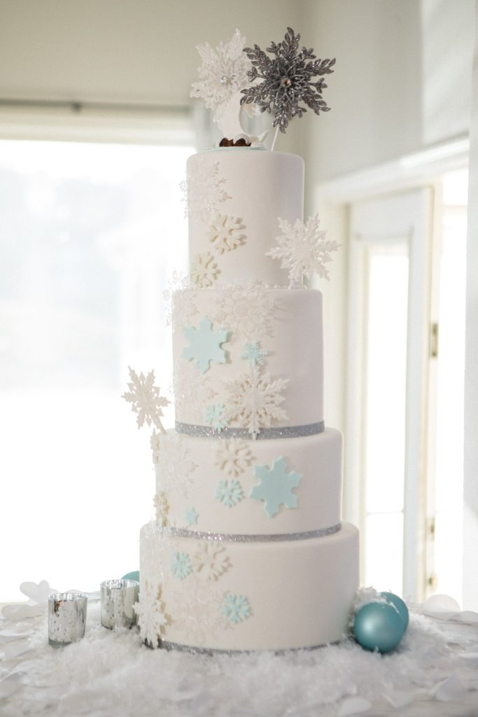 white four layer cake covered in snowflakes for winter baby shower