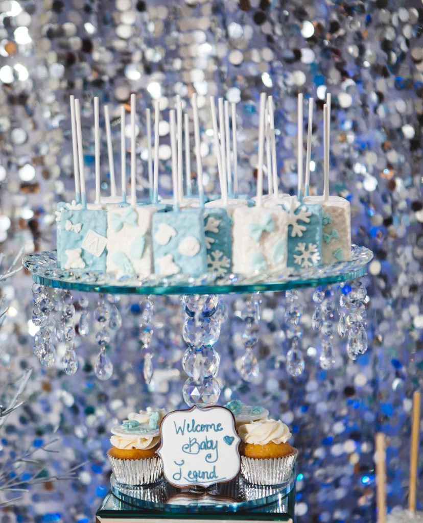 blue and white rice krispie treats on baby shower dessert table