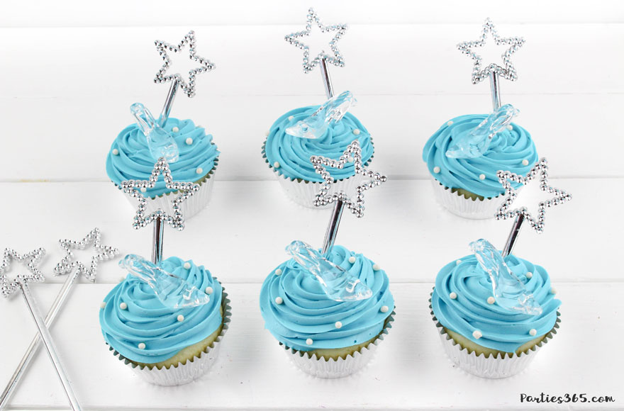adding white sprinkles to blue cinderella cupcakes