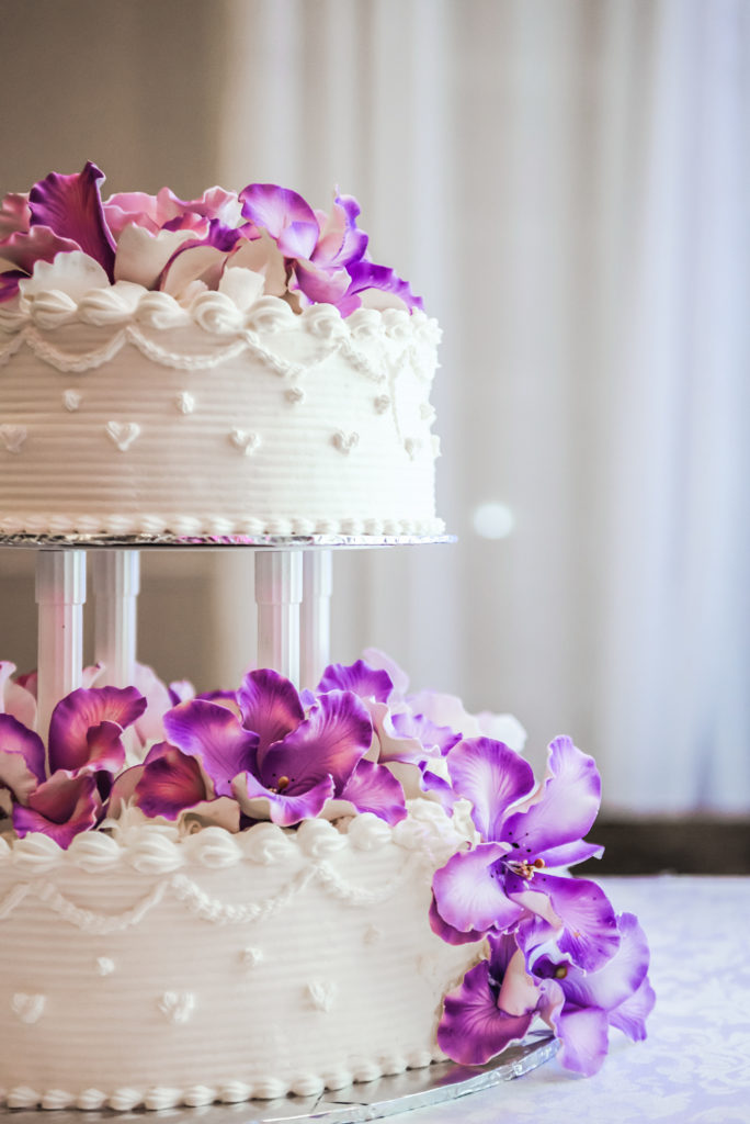 two tiered white birthday cake covered in purple orchid flowers