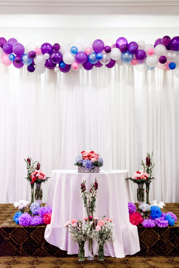 purple white and blue balloon arch on white background