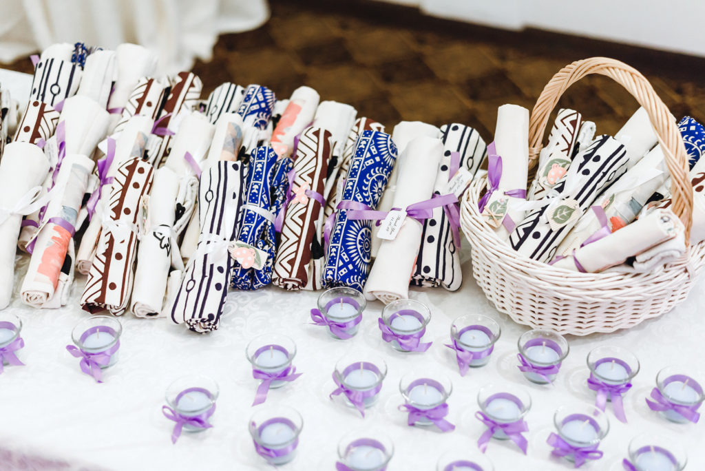 party favor table with fabric backpacks and purple candles