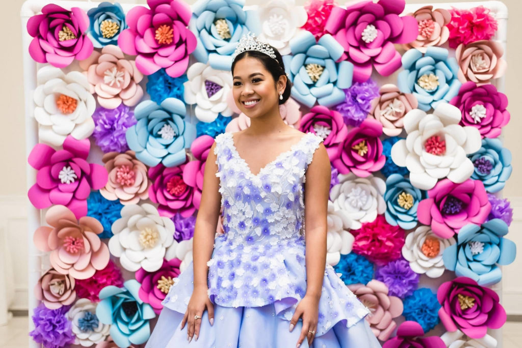 Filipino 18th birthday girl in purple dress standing in front of paper flower wall